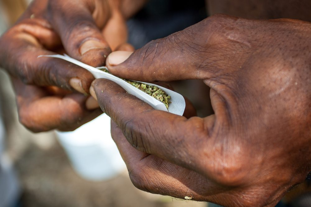 holding in a toke represented by black person's hands rolling joint