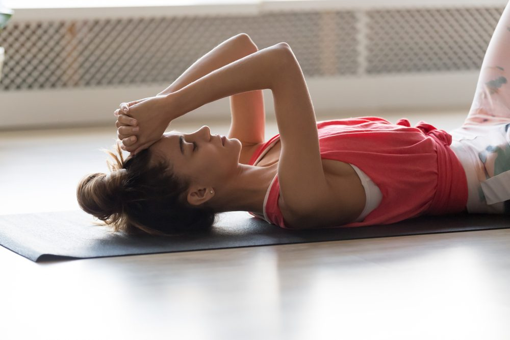 slimming down with cbd represented by younger female stretching on back on yoga mat
