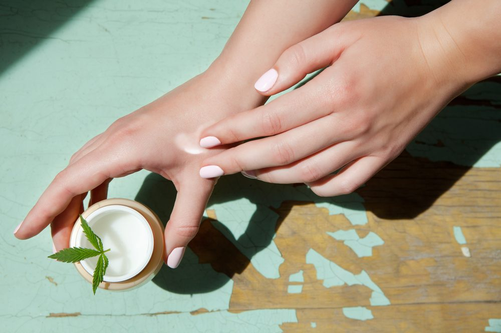 winter skin care represented by person spreading cannabis cream on hand
