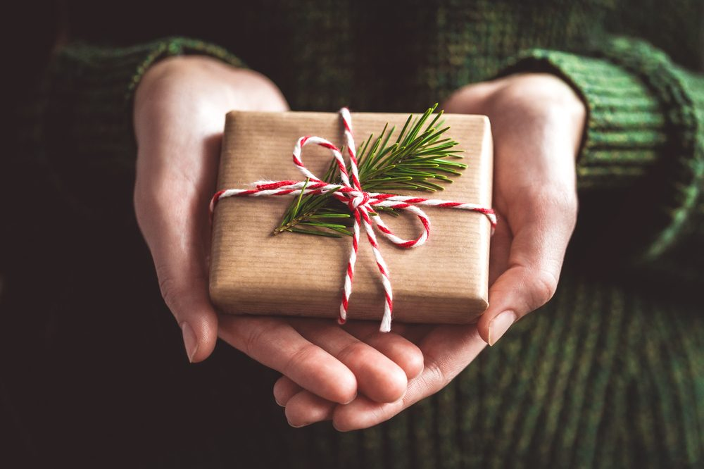 christmas weed represented by hands holding brown wrapped box with sprig of pine in ribbon