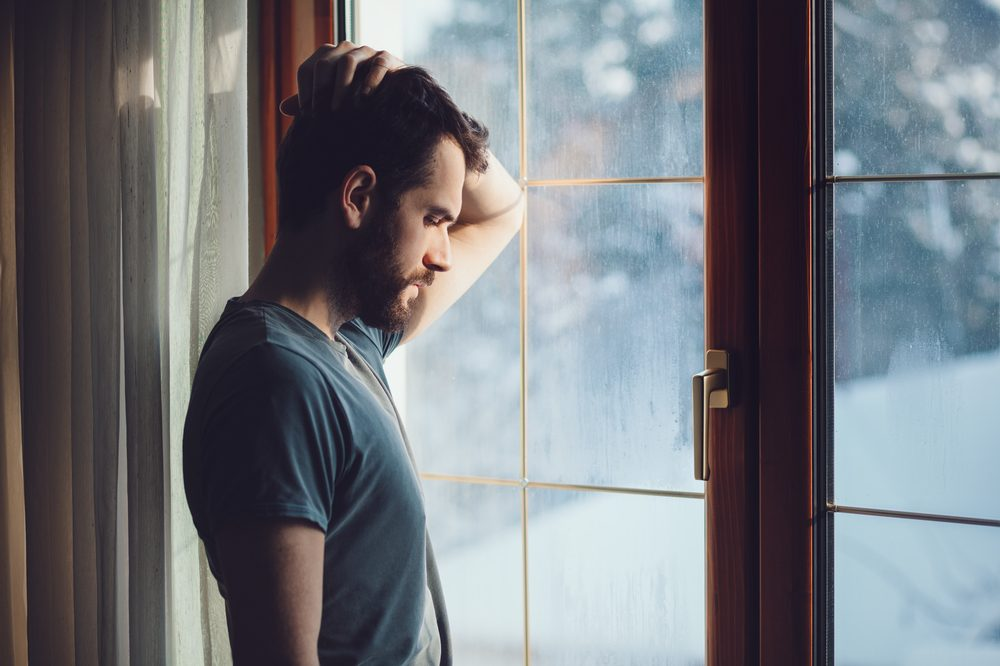 sad young man standing against a window looking outside