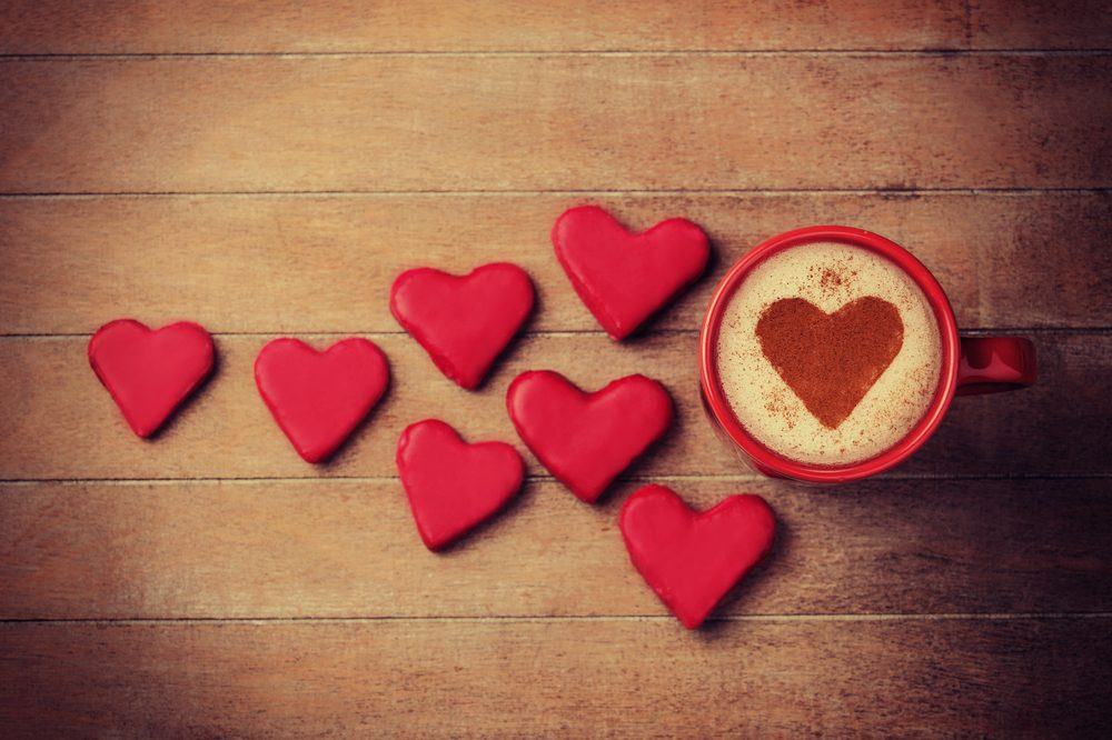 cut out hearts next to cup of coffee with heart in it.