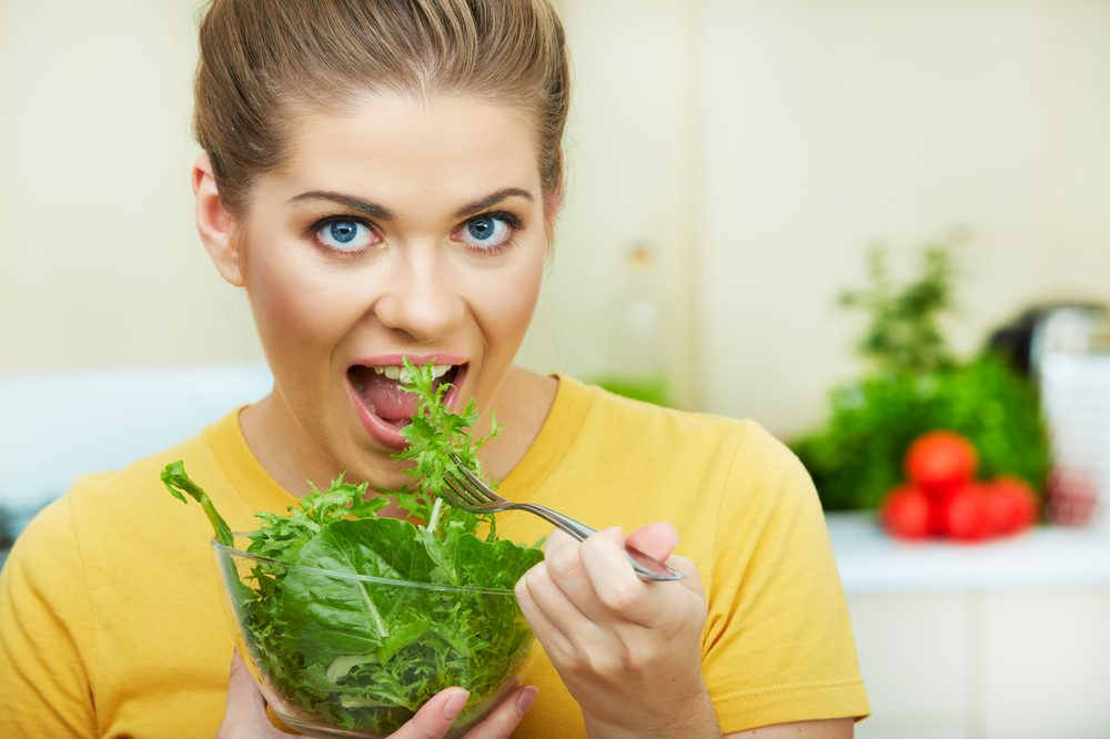 young woman eating salad to represent flavonoids in cannabis