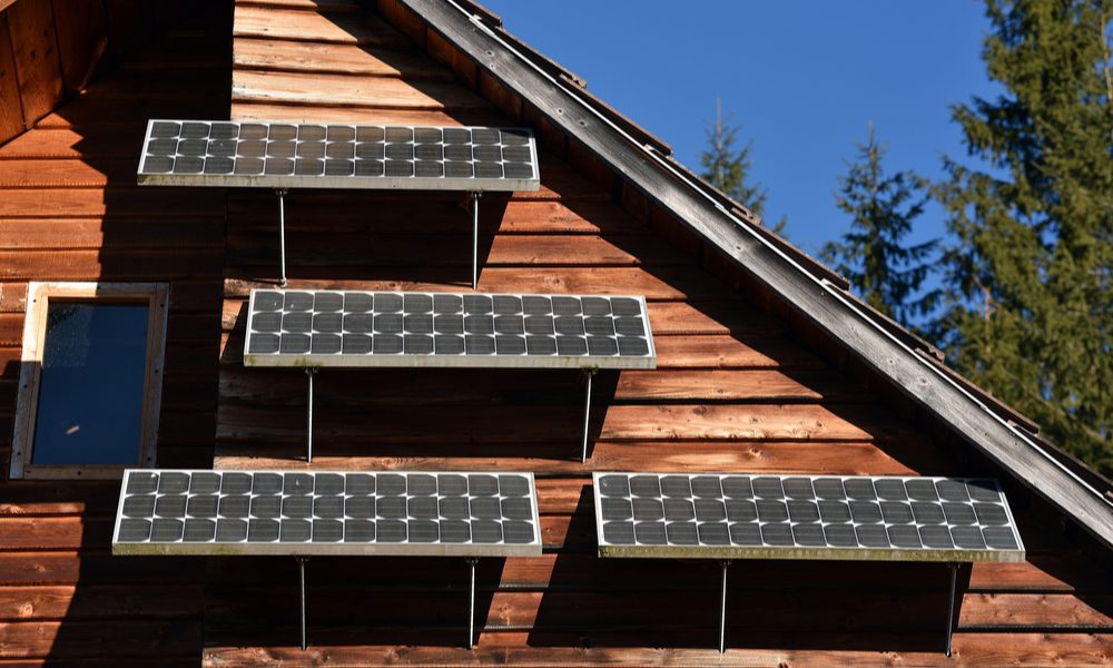 living off grid represented by solar panels on a cabin