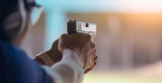 oklahoma gun laws represented by man holding gun at firing range
