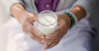 hemp milk in glass in older white woman's hand