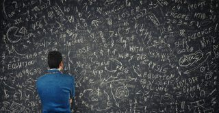 chart thc percentage represented by man with back to camera working on black board with lots of calculationsusing